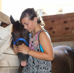 Austin Kirkpatrick, 12, of Rimersburg, shows affection to her horse, Jewels, after a morning of competing. (By Leisel Kober)