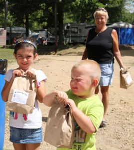 Miah Shingledecker, 4, and Korbin Baker, 2, receive their free lunches Tuesday at the Venango County Fair. The lunches were provided by Local United Methodist Churches and included a ham and cheese sandwich, fresh veggies, apple, chips and cookies with a small Bible pamphlet. (By Leisel Kober.)
